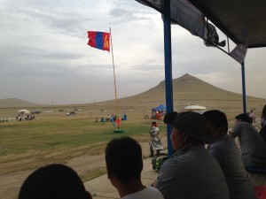 The Mongolian flag and my training site's sacred mountain, as seen from the Naadam stadium